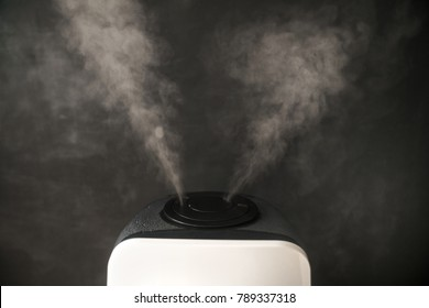 humidifier ultrasonic digital distributes steam in the living room against the background of a black chalkboard.