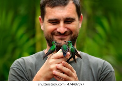 Hummingbirds on human hand. Nature holiday in Costa Rica. Wildlife scene from tropical forest. Green-crowned Brilliant, Heliodoxa jacula feeding on nectar.