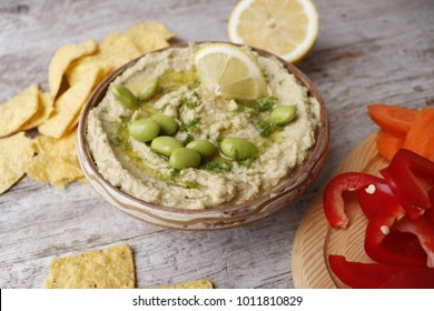 Hummus with avocado and beans edamame. Sliced fresh vegetables and crisps from corn tortilla.