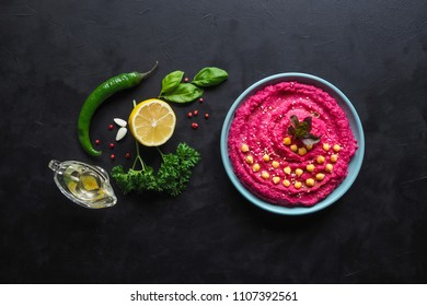 Hummus with beetroot on a black kitchen table