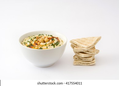 Hummus in bowl with pita bread isolated on white background