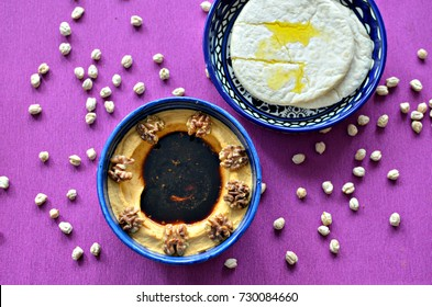 Hummus with caramelized walnuts, pomegranate molasses and pita bread, top view, purple background.