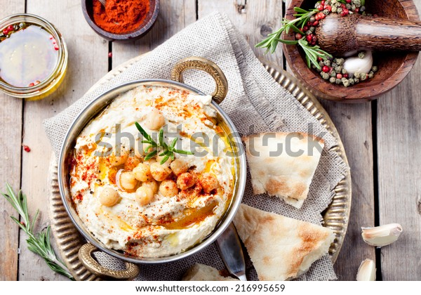 Hummus, chickpea dip, with rosemary, smoked paprika and olive oil in a metal authentic bowl with pita on a wooden background.