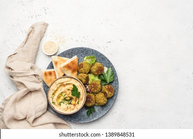 Hummus chickpea, falafel and pita bread. Arabic cuisine food, vegan appetizer. Top view on grey concrete background with copy space
