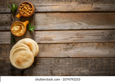 Hummus and chickpeas snack with shaverma (or shavarma, pita). Wooden planks background. Middle East cuisine
