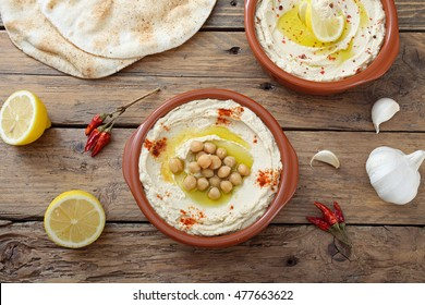 hummus dip in ceramic bowl on wooden table