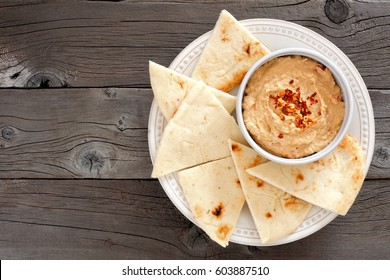 Hummus dip with pita bread on a plate, above view on a rustic wooden background