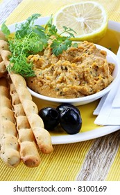 Hummus dip served with lemon, cilantro or coriander, black olives and bread sticks.