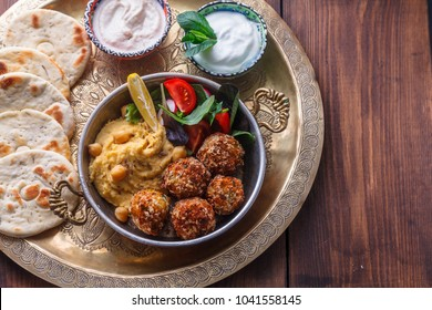 Hummus, falafel, salad in a pan with yoghurt and tahini