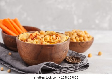 Hummus, fresh carrot sticks and boiled chickpeas in wooden bowls. Vegan food concept, light background
