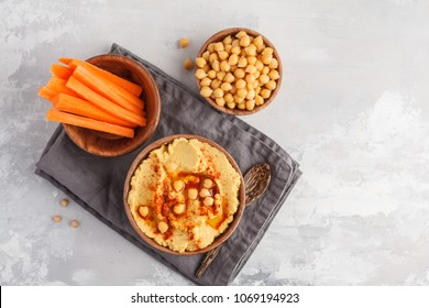 Hummus, fresh carrot sticks and boiled chickpeas in wooden bowls. Vegan food concept, light background, top food