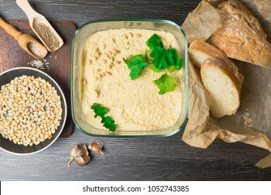 Hummus or houmous, appetizer made of mashed chickpeas with tahini, lemon, garlic, olive oil, parsley, cumin on wooden table