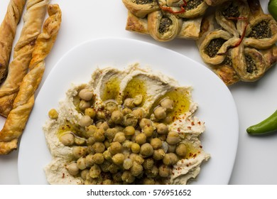Hummus or Houmous traditional Syrian food plate mostly for breakfast with some pastries.Oriental recipe. olive oil, chick peas, sesame paste, lemon, garlic, salt, cumin