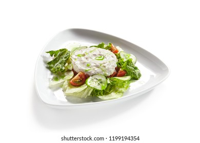 Hummus, Humus or Hommos with Cucumbers, Tomatoes and Lettuce Salad Isolated on White Background. Levantine Dip or Spread made from Chickpeas, Tahini, Olive Oil, Lemon Juice, Salt and Garlic Close Up