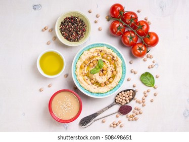 Hummus ingredients. Chickpea, tahini paste, olive oil, sesame seeds, sumac, herbs on white rustic wooden background. Set of raw ingredients for making hummus. Middle eastern cuisine. Top view
