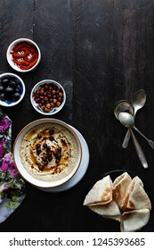Hummus made with black chickpea vegan and natural nutrition lunch dip paste with pita bread, paprika, sesame and olive on rustic wooden background. flat lay. Healthy dietary fiber protein food