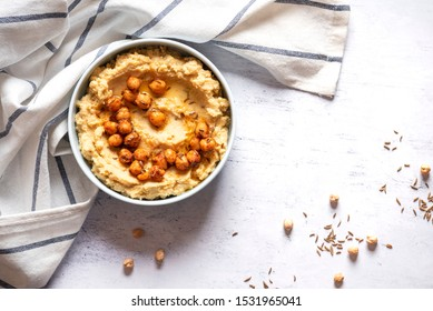 Hummus with olive oil and chickpeas in a ceramic bowl on a light grey background, top view. Traditional middle eastern snack hummus, healthy food, vegetarian food.