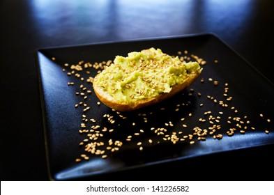 Hummus on toasted bread with sesame seeds