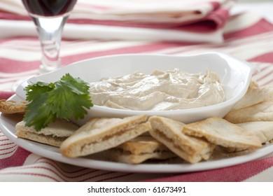 Hummus plate with pita chips and cilantro garnish.