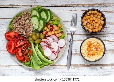 Hummus platter with assorted snacks. Hummus in bowl, vegetables sticks, chickpeas, olives. Plate with Middle Eastern/Mediterranean meze. Party/finger food. Top view. Vegetables, hummus dip,copy space