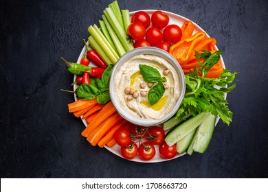 Hummus platter with assorted snacks. Hummus in bowl and vegetables sticks. Plate with Middle Eastern. Party, finger food. Top view. Vegan, hummus dip