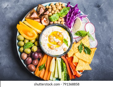 Hummus platter with assorted snacks. Hummus in bowl, vegetables sticks, chickpeas, olives, pita chips. Plate with Middle Eastern/Mediterranean meze. Party/finger food. Top view. Vegetables, hummus dip