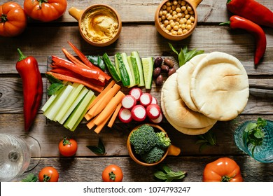 Hummus and variety of vegetable sticks. Healthy snacks. Wooden planks background