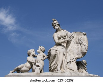 Humorous classical stone statue of a maiden and cherubs on which someone has tied a face mask in a pollution and health concept against a sunny blue sky