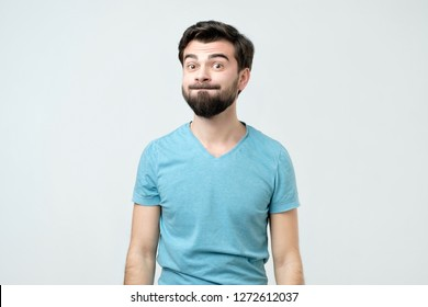Humorous emotional portrait of grimacing young man.
