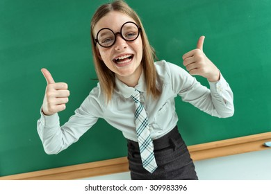 Humorous high angle view of Happy young schoolgirl has her thumbs up / photo of teen school girl wearing glasses, creative concept with Back to school theme