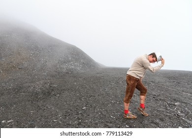Humorous individual moonwalking in a moonlike landscape in the mountains of the Swiss alps near Grimentz, Switzerland, on a cloudy day in summer in traditional clothing