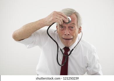 Humorous medical concept of a senior man pulling a comical face holding a stethosope to his forehead as though checking his brain function, intellect, wisdom or cognitive powers