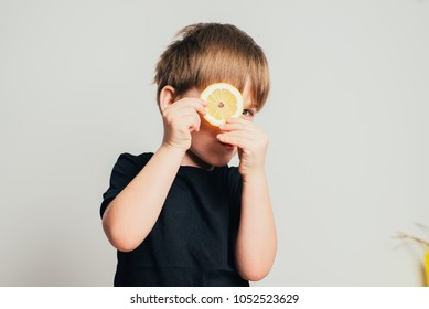 Humorous Nutrition Themed Concept Image of Smiling Boy with Wavy Blond Hair Holding Slices of Lemons Over Eyes in Studio with Gray Background and Copy Space