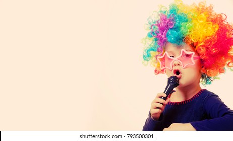 Humorous photo. Cute child girl singing with a microphone (Happy childhood, teaching singing, music, child development concept)