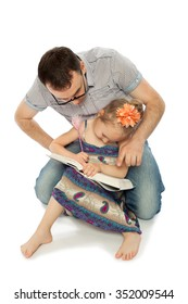 Humorous photo. Dad wore glasses , he looks on as his daughter draws in the book - Isolated on white background
