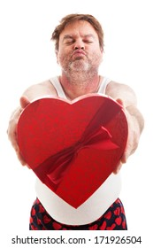 Humorous photo of a scruffy looking middle aged man in his underwear holding a box of Valentines day candy and waiting for a kiss. Isolated on white.