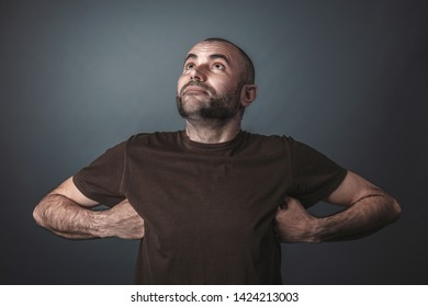 Humorous portrait of Caucasian man looking up and with arms raised and hands under armpits. Proud and satisfied look.