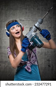 Humorous portrait of a housewife using a jackhammer to drill into wall