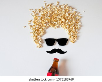 Humorous portrait of the moviegoer wearing glasses, a drink in a bottle and a popcorn hairstyle