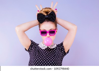 Humorous portrait of a young woman making a bubble of chewing gum with fingers in a V behind her head