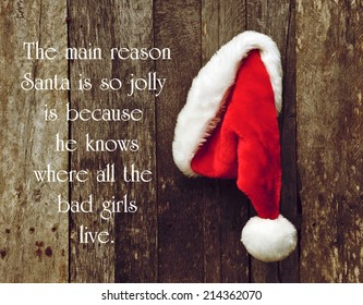 Humorous quote about Santa Clause by George Carlin, with Santa's hat hanging on a rustic wooden wall.