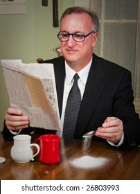Humorous scene of a business man dressed in a suit and tie sitting down to morning coffee reading the newspaper and absentmindedly missing the cup as he adds sugar to his coffee.