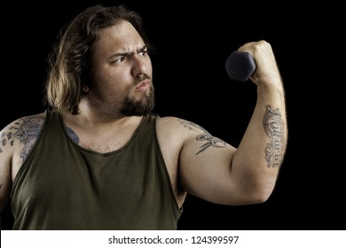 Humorous shot of a large man with tattoos lifting a very small weight