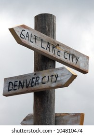 Humorous weathered signs pointing toward Denver and Salt Lake City