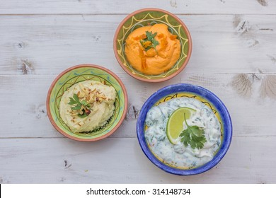 Humus and tzatziki on a white wooden table