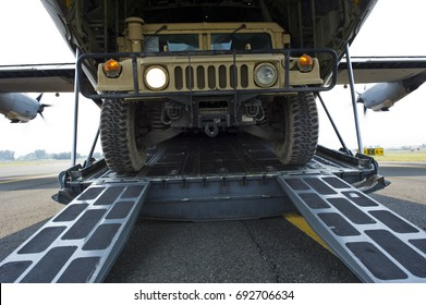 Humvee vehicle is offloaded from a cargo aircraft.