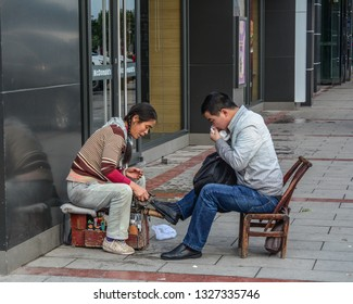 Hunan, China - Nov 2, 2015. Shoeshiner polishing the shoes on street in Hunan, China. Hunan located in the middle reaches of the Yangtze watershed in South Central China.