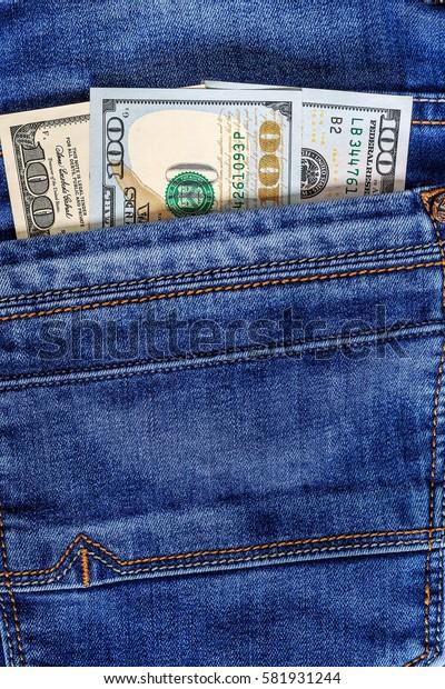Hundred dollar bill in the pocket of  blue jeans. Cash money.