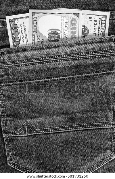 Hundred dollar bill in the pocket of  blue jeans. Cash money. Black and white image.