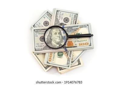 hundred dollar bills and magnifying glass on a white background. Top view.